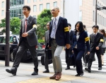 In this Oct. 14, 2016 photo, officials from the Tokyo Labor Bureau head to the headquarters of Japan's top ad agency, Dentsu, in Tokyo for on-site inspections. (Akiko Matsushita/Kyodo News via AP)