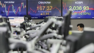 A currency trader works near screens showing the Korea Composite Stock Price Index (KOSPI), right, and the foreign exchange rates at the foreign exchange dealing room in Seoul, South Korea on Tuesday, Oct. 25, 2016. (AP / Lee Jin-man)