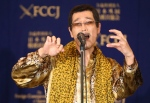 Japanese comedian Pikotaro performs 'pen-pineapple-apple-pen' song at a press conference in Tokyo, Friday, Oct. 28, 2016. Pikotaro said he is astonished by the global success of the song. (AP Photo/Eugene Hoshiko)