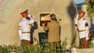 "Cuba's President Raul Castro places the ashes of his older brother Fidel Castro into a niche in his tomb, a simple, grey, round stone about 15 feet high at the Santa Ifigenia cemetery in Santiago, Cuba, Sunday Dec.4, 2016. The niche was then covered by a plaque bearing the single name,""Fidel.""(Marcelino Vazquez Hernandez/Pool Photo via AP)"