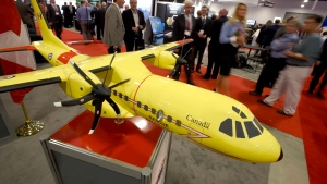 Delegates pass a model of the Airbus C295 fixed wing search and rescue aircraft at the Canadian Association of Defence and Security Industries' CANSEC trade show in Ottawa on Wednesday, May 27, 2015. (Justin Tang / THE CANADIAN PRESS)