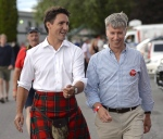 Liberal Leader Justin Trudeau speaks to retired general Andrew Leslie at the Glengarry Highland Games in Maxville, Ont., on Aug. 1, 2015.The prime minister is formally recruiting retired soldier-turned-Liberal MP Andrew Leslie to help manage Canada's relationship with the United States. (Justin Tang / THE CANADIAN PRESS)