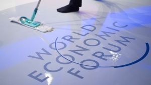 A woman cleans the stage prior to a panel session on the closing day of the 47th annual meeting of the World Economic Forum, WEF, in Davos, Switzerland, Jan. 20, 2017. (Gian Ehrenzeller / Keystone via AP)