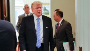 U.S. President Donald Trump walks in from the Oval Office of the White House in Washington in Washington, Monday, Jan. 23, 2017, before hosting breakfast with business leaders in the Roosevelt Room. Sitting at the table is White House Senior Adviser Steve Bannon, left, and Kevin Plank, founder, CEO and Chairman of Under Armour. (AP Photo/Pablo Martinez Monsivais)