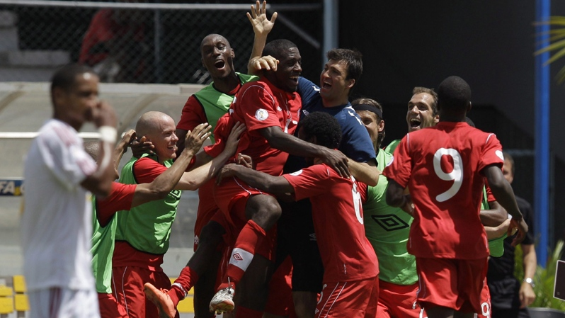 Canada's players celebrate after Oliver Ocean, partially covered by teammates,scored against Cuba during a 2014 World Cup qualifying soccer game in Havana, Cuba, Friday June 8, 2012. (AP Photo/Franklin Reyes)