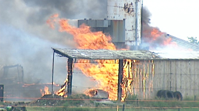 Firefighters battle a blaze at a woodworking shop north of Elmira, Ont. on Tuesday, July 17, 2012.
