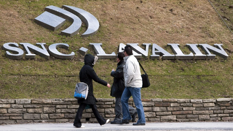 Pedestrians walk past the offices of SNC Lavalin in Montreal. (Ryan Remiorz / THE CANADIAN PRESS)