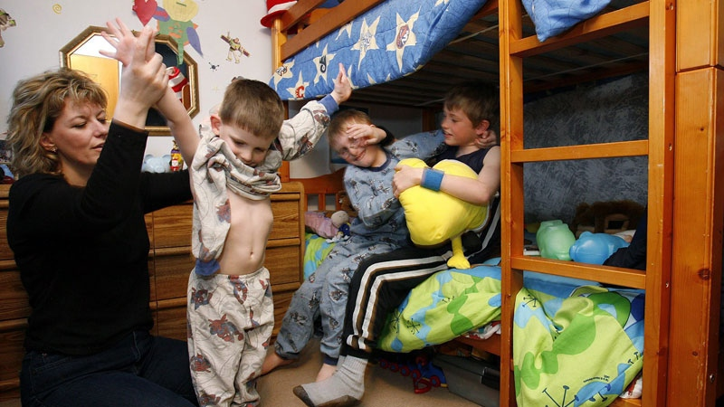 Lise Cook puts on three year old Jonah's pyjamas while her two other sons Jeremie (6) (L) and Patrick (9), wrestle on their bed in Winnipeg. (CP PHOTO/John Woods) CANADA
